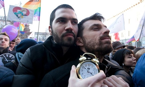 Two men hugging at a street parade and holding a clock